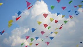 Mång--färgade flaggor som svänger i vind på bakgrund av moln lager videofilmer