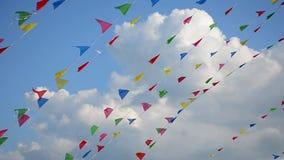 Mång--färgade flaggor som svänger i vind på bakgrund av moln stock video
