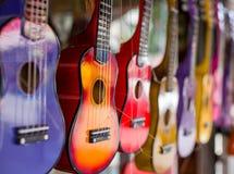 Mång--färgade gitarrer Små gitarrer av olika färger Bilden togs på den öppna öppningen En gitarr i den fokusen royaltyfria foton