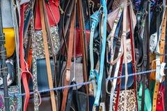 Mång--färgade handväskor och bälten som är handgjorda i fönstret av en gatuförsäljare royaltyfria foton