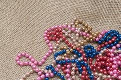 Mång--färgade pärlor på ett bakgrundstyg Royaltyfri Foto