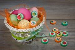 Mång--färgade påskägg och sötsaker i en härlig korg arkivbild