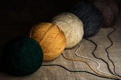 Mång--färgade woolen clews på en säckväv Arkivbilder