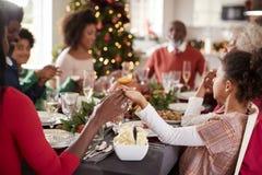 Mång- familj för blandat lopp för utveckling som sitter på julmatställetabellen som rymmer händer och säger upp nåd, selektiv fok arkivbilder