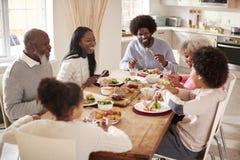 Mång- familj för blandat lopp för utveckling som tillsammans äter deras hemmastadda söndag matställe, högstämd sikt royaltyfri fotografi