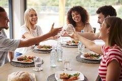 Mång- folkgrupp av fem lyckliga unga vuxna vänner som skrattar och lyfter exponeringsglas för att rosta under ett matställeparti arkivbild