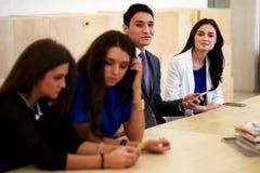 Mång- folkgrupp av intelligenta internationella studenter som arbetar på celltelefonen under avbrott mellan föreläsningar Arkivbilder
