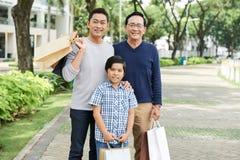 Mång--generationsbunden asiatisk familj med pappers- påsar royaltyfria bilder