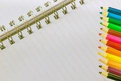 Mång- kulöra blyertspennor och anteckningsbok med det tillbaka tangentbordet vid fokusen på blyertspennan Fotografering för Bildbyråer