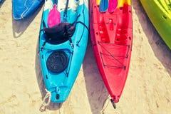 Mång- kulöra kajaker med skovlar på sanden nära havet Top besk?dar royaltyfri foto