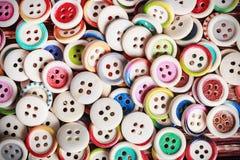 Mång- kulöra knappar på en träbakgrund royaltyfri fotografi
