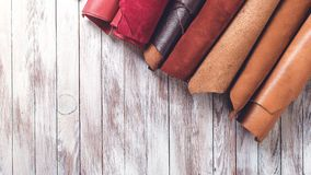 Mång- kulört läder i rullar Lekmanna- lägenhet Rolls av naturligt färgläder Material för läderhantverk kopiera avstånd Top beskåd arkivfoton