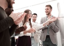 Mång--person som tillhör en etnisk minoritet affärslag som applåderar till högtalaren efter presentation på nytt projekt arkivbild