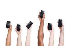 Mång--person som tillhör en etnisk minoritet armar som ut lyfter Smartphones och ett anseende arkivfoton