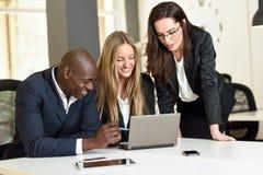 Mång--person som tillhör en etnisk minoritet grupp av tre businesspeople som möter i en modern nolla arkivbilder