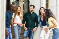 Mång--person som tillhör en etnisk minoritet grupp av vänner som har gyckel tillsammans i stads- backg royaltyfria bilder