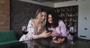 Mång- person som tillhör en etnisk minoritet två vändamer i pyjamas på kökstångtabellen med exponeringsglas för ett vin som ser t arkivfilmer