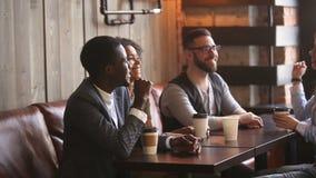 Mång--person som tillhör en etnisk minoritet unga vänner som visar att ge sig för enhet som är högt-fem på kafémötet stock video