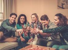 Mång--person som tillhör en etnisk minoritet vänner med pizza och flaskor av drinken Royaltyfri Bild