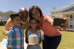 Mång--utveckling familj som tar selfie med mobiltelefonen, medan fira födelsedag av grandaughter royaltyfri fotografi