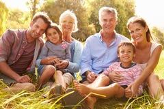 Mång--utveckling familj som tillsammans utomhus kopplar av royaltyfri bild