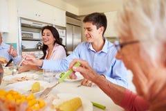 Mång--utveckling familjsammanträde runt om tabellen som äter mål royaltyfria bilder