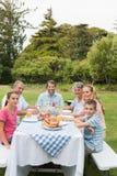 Mång- utvecklingsfamilj på picknicktabellen som har matställen utanför Royaltyfria Bilder