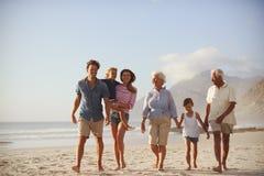 Mång- utvecklingsfamilj på semester som tillsammans promenerar stranden royaltyfri bild