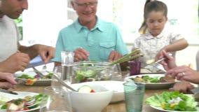 Mång- utvecklingsfamilj som äter mål runt om köksbordet arkivfilmer