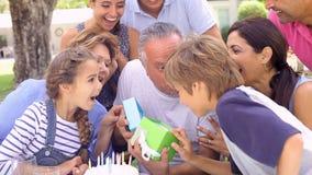 Mång- utvecklingsfamilj som firar födelsedag i trädgård arkivfilmer