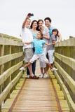 Mång- utvecklingsfamilj som går på bron som tar fotoet Royaltyfri Bild
