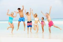 Mång- utvecklingsfamilj som har gyckel i havet på strandferie Arkivbild