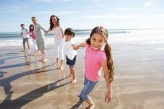 Mång- utvecklingsfamilj som har gyckel på strandferie Arkivbild
