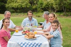 Mång- utvecklingsfamilj som har matställen utanför på picknicktabellen Arkivbilder