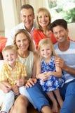 Mång- utvecklingsfamilj som hemma kopplar av på sofaen Arkivbilder