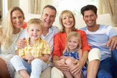 Mång- utvecklingsfamilj som hemma kopplar av på sofaen Royaltyfria Bilder
