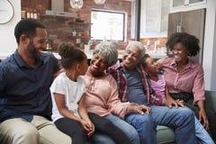 Mång- utvecklingsfamilj som kopplar av på Sofa At Home Together royaltyfri foto