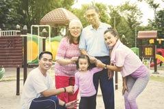 Mång- utvecklingsfamilj som ler i lekplatsen royaltyfria bilder