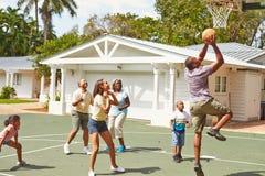 Mång- utvecklingsfamilj som spelar basket tillsammans Fotografering för Bildbyråer