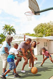 Mång- utvecklingsfamilj som spelar basket tillsammans Arkivbilder