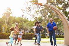 Mång- utvecklingsfamilj som spelar basket tillsammans Royaltyfri Fotografi