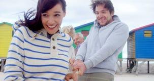 Mång- utvecklingsfamilj som spelar dragkampen på stranden stock video