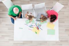 Mång- utvecklingsfamilj som tillsammans gör konsthantverk Arkivfoton
