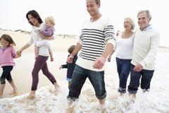 Mång- utvecklingsfamilj som tillsammans promenerar stranden Royaltyfria Foton