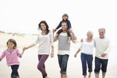 Mång- utvecklingsfamilj som tillsammans promenerar stranden Royaltyfri Foto