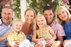Mång- utvecklingsfamilj som tillsammans sitter på sofaen Fotografering för Bildbyråer