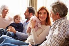 Mång- utvecklingsfamiljsammanträde på Sofa With Newborn Baby Royaltyfria Foton
