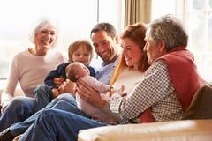 Mång- utvecklingsfamiljsammanträde på Sofa With Newborn Baby Royaltyfri Foto