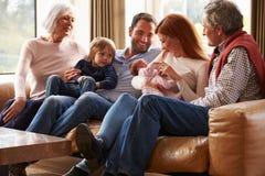 Mång- utvecklingsfamiljsammanträde på Sofa With Newborn Baby Arkivfoto