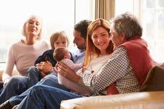 Mång- utvecklingsfamiljsammanträde på Sofa With Newborn Baby Royaltyfri Fotografi